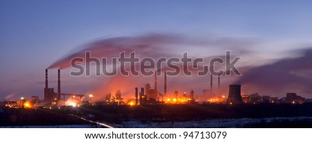 Panorama of the chemical factory in the evening, with lights and smoke, long exposure - stock photo