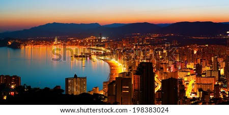 Panorama of the city with an empty sea beach on a background of mountains in sunset (Spain, Benidorm) - stock photo