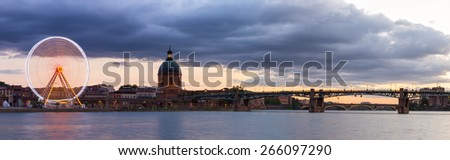 Panorama of the Ferris Wheel and  Hopital de La Grave and Pont Saint-Pierre in Toulouse - stock photo
