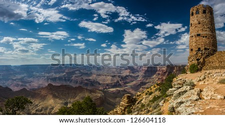 Panorama of the grand canyon with a blue sky and white clouds and the Desert View watchtower to the right of the image