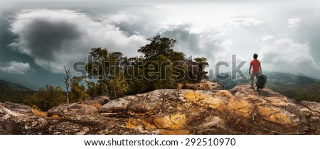 Panorama of the hiker with backpack standing on the rocky ground of the mountain - stock photo