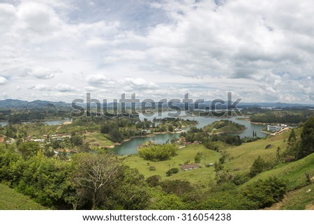 Panorama of the lakes and islands in Guatape taken from Piedra el Penol with cloudy sky, near Medellin, Colombia. - stock photo