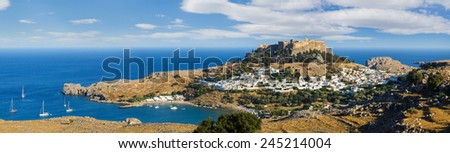 Panorama of the Lindos town and Acropolis on the island of Rhodes under puffy clouds, Greece - stock photo