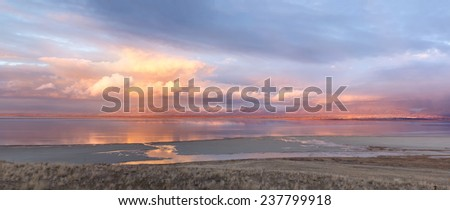 Panorama of the mountains in the clouds reflected in their Salt Lake and Ogden (Utah) in the last rays of the sun - stock photo