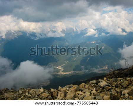 Panorama of the mountains in the Krasnaya Polyana area of the city of Sochi. Clouds, air haze, trees