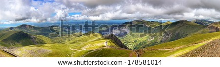 Panorama of the mountains of Snowdonia, looking from Mount Snowdon along the mountain railway track towards the town of Llanberis - stock photo