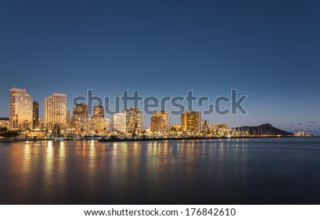 Panorama of the nightime skyline of Honolulu and Waikiki from Ala Moana park after the sun sets with lights illuminating the facades of the hotels and apartments - stock photo