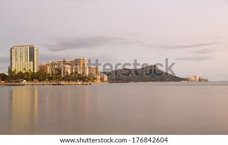 Panorama of the skyline of Waikiki at sunset or dusk taken with a long exposure to blur out movement in the water and provide a reflection of Diamond Head in Hawaii - stock photo