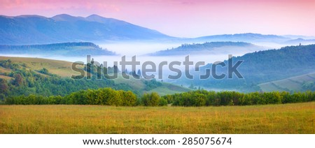 Panorama of the sunny summer morning in the foggy Carpathian mountains. Borzhava ridge, Transcarpathian, Ukraine, Europe. - stock photo