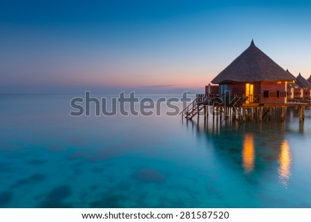 Panorama of tropical island resort with over water bungalows at night. Ari Atoll. - stock photo