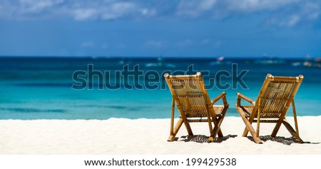 Panorama of two bamboo chairs on a beautiful tropical beach with white sand and clear turquoise ocean at exotic island in Philippines - stock photo