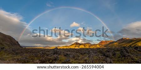 Panorama of volcanic landscape under a full rainbow, Landmannalaugar, Iceland   - stock photo