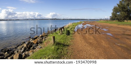 Panorama of water puddles in the gravel road  near    the calm waters of the Leschenault Estuary  near Australind Western Australia on an early morning in late autumn. - stock photo