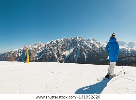 Panorama of winter sport snow mountain landscape with ski woman.