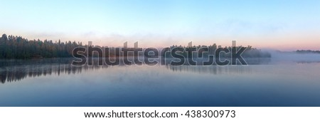 panorama of wood lake with morning fog