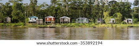 Panorama of wooden houses on stilts and Indian natives on the Amazon river bank near Manaus with the rain forest in the background. Amazonas State. Brazil 2015 - stock photo
