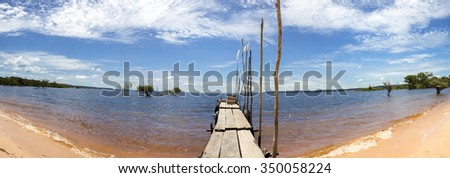 Panorama of wooden pier and sand beach on the Amazon River with clear blue sky near Manaus, Amazonas State. Brazil 2015 - stock photo