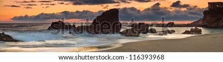 Panorama of Woods Cove Sunset Panoramic seascape of sunset at Woods Cove, Laguna Beach, California. - stock photo