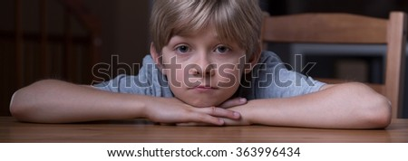 Panorama of young boy in pensive mood alone - stock photo