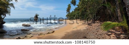 Panorama on a beautiful sandy beach with rocky islet and tropical vegetation, Caribbean sea, Costa Rica - stock photo