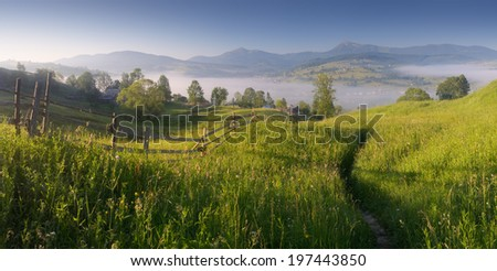 Panorama on a sunny morning. Mountain village with mist. Trail in the grass. Carpathians, Ukraine, Europe - stock photo