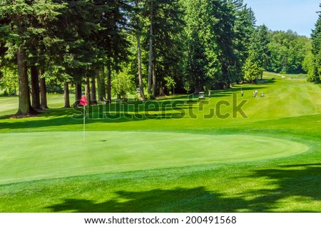 Panorama, outlook at the beautiful golf course in a sunny day with red flag. Canada, Vancouver. - stock photo