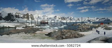 Panorama - penguin colonies, cruise ship & tourists,Petermann Island,Antarctica - stock photo
