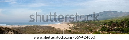 Panorama sea, beach, dunes and mountains in Guincho beach in Portugal with low clouds in the evening