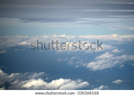 Panorama spectacular skyline view above sea of clouds in blue sky from airplane window over breath-taking tranquil earth background, horizontal picture  - stock photo