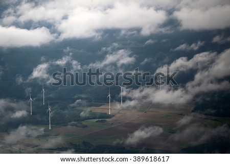 Panorama spectacular skyline view of cloudy blue sky from airplane window over windfarm landscape background wind turbines renewable power energy stations, horizontal picture
