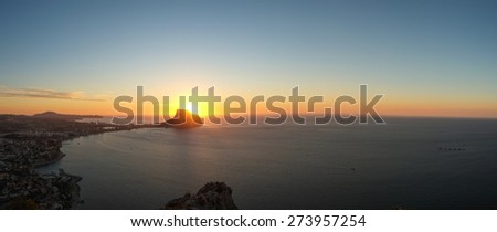 Panorama take of a scenic sunrise on Calpe bay, Costa Blanca, Spain - stock photo