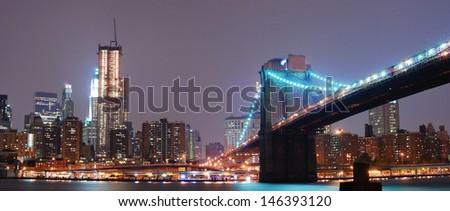 Panorama view. New York City Manhattan skyline with Brooklyn bridge at night. - stock photo