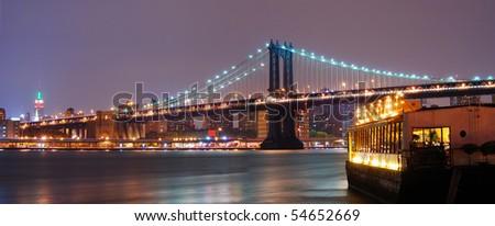 Panorama view. New York City Manhattan skyline with Manhattan bridge and boat at night. - stock photo