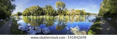 Panorama view of Autumn colored trees reflecting into Lake. Princess Island Park, Calgary, Alberta, Canada - stock photo