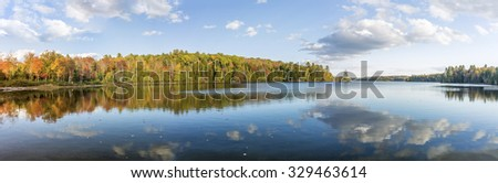 Panorama View of Fall Colors Reflecting on the Surface of a Lake - Algonquin Provincial Park, Ontario, Canada   - stock photo