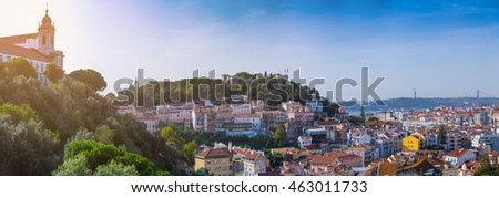 Panorama view of old town Lisbon and Sao Jorge Castle, the capital and the largest city of Portugal. Evening landscape in backlit sunset sunbeam.