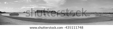 panorama view of sea and beach with traditional boat, bridge, long mountain in background, black and white picture style. Grain added - stock photo