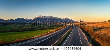 Panorama view of the High Tatra mountains with mount Krivan and a local highway in Slovakia at sunset - stock photo