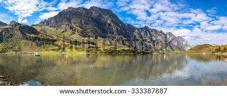Panorama view of Truebsee (lake) on a sunny summer day with Braustock in background and beautiful reflection in water, canton of Nidwalden, central Switerland.