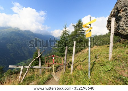 "Panorama with footpath, signposts with alpine hut names and German text ""Danger, don't leave steep path! kids under supervision, dogs on a leash!"" and mountains in the Alps, Austria - stock photo"
