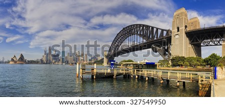 panorama with Kirribilli ferry pier, Sydney Harbour bridge and cityline of skyscrapers on a sunny summer day across harbour water - stock photo