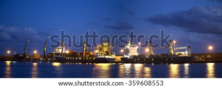 Panorama with ships and cranes near night pier with illumination