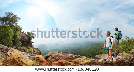 Panorama with two male backpackers standing on top of a mountain and looking to a valley - stock photo