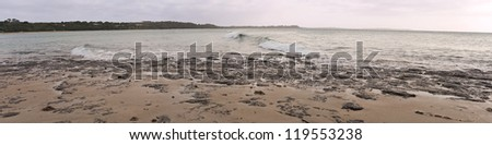 Panorama with wave breaking in the middle, rising sun on one side, black rocks, sand and shoreline in background in Victoria, Australia - stock photo