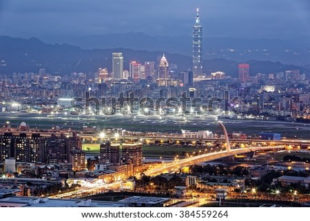 Panoramic aerial view of busy Taipei City, Keelung River, Dazhi Bridge, Songshan Airport & 101 Tower in XinYi District at dusk ~ A romantic evening of Taipei with beautiful blue twilight in the sky - stock photo
