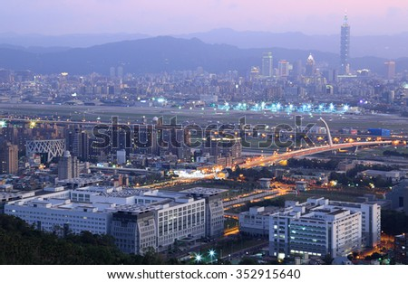 Panoramic aerial view of busy Taipei city, Keelung river, Dazhi Bridge, Songshan Airport and XinYi District at dusk ~ A romantic evening of Taipei downtown, with beautiful rosy afterglow in the sky - stock photo