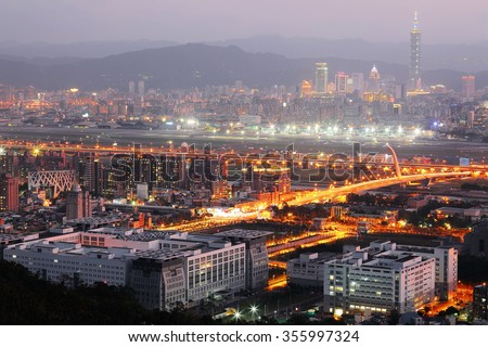 Panoramic aerial view of busy Taipei City, Taipei 101, Songshan Airport, XinYi Commerical  District, Dazhi Bridge and downtown in rosy evening twilight ~ A moody nightscape of Taipei   - stock photo
