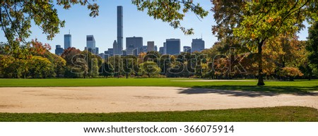 Panoramic afternoon view of Central Park Great Lawn with fall foliage and Manhattan Midtown skyscrapers in the distance. New York City - stock photo