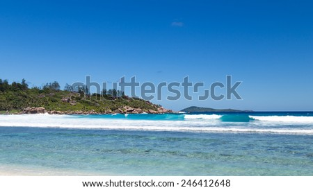 Panoramic beautiful seascape and sea waves with white foam rolls on a tropical beach island of La Digue, Seychelles - stock photo