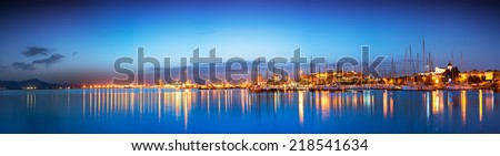 Panoramic cityscape at blue hour with reflection in the sea  - stock photo